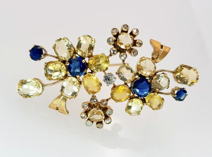 Yellow gold brooch of 18 kt with 4 sapphires, 2 topazes, 17 diamonds and 14 quartzes IGE certificate