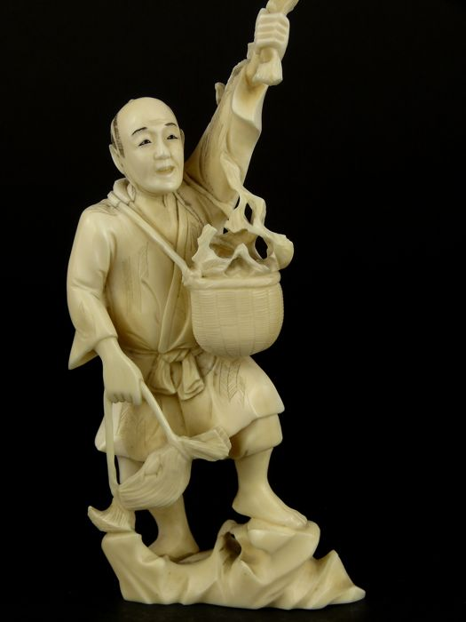 An ivory okimono of a man picking persimmons - Japan - ca. 1900 (Meiji Period)