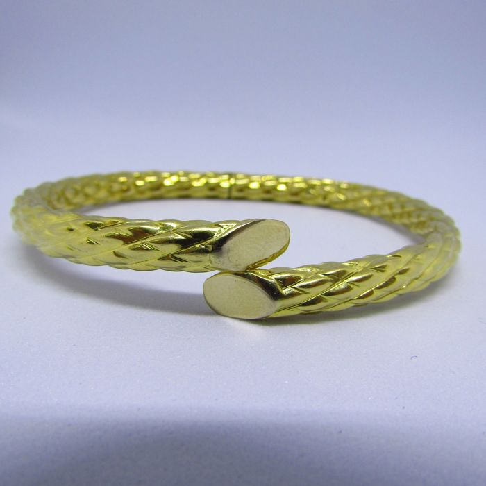 Oval and rigid bracelet in bi-colour gold of 18 kt, open and adjustable Measurements: 70 x 60 mm Weight: 20.60 g