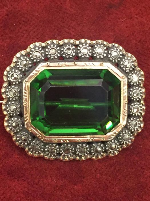 Silver brooch with green stone