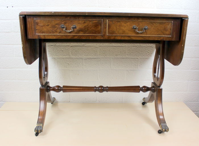 Walnut Regency-style writing table with 2 drawers and resting on claw legs with wheels - England - from the end of the 19th century