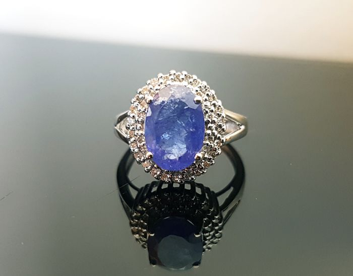 14 kt white gold entourage ring with tanzanite accompanied by 52 SI1 / G-H round cut diamonds - ring size: 16.6