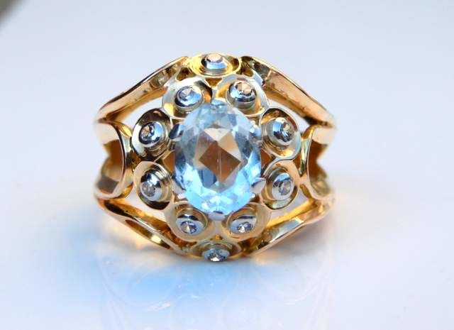 Ball ring made of 18 kt yellow gold and platinum, volute motifs set with diamonds, aquamarine in the center