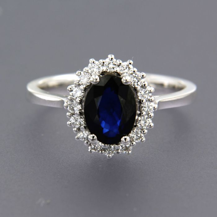 - no reserve price - 18 kt white gold entourage ring set with a central blue sapphire of approx. 1.36 ct in total and 16 brilliant cut diamonds of approx. 0.32 ct in total