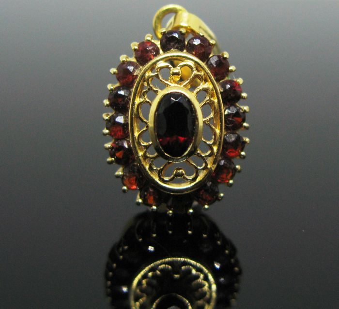Yellow gold 18 kt pendant set with entourage of 16 red garnet round-faceted cut and 1 marquise faceted-cut  tot 0,65 ct. No reserve price
