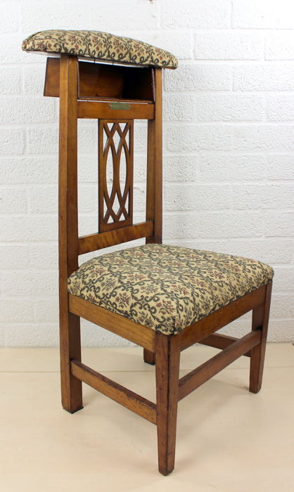 Antique prayer chair with fabric upholstery and nameplate