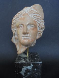A stone carved Greek head on marble stand, second half 20th century