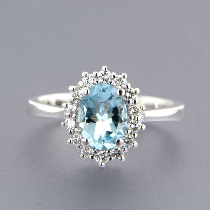 14 kt white gold rosette ring set with a central oval cut blue topaz, and 14 brilliant cut diamonds, ring size 16.5 (52)