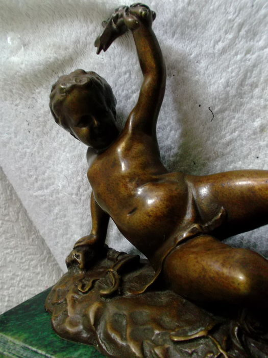Alexandre Falguière (1831-1900) - a patinated bronze statue of a reclining putto on a green marble base - France - end of 19th century