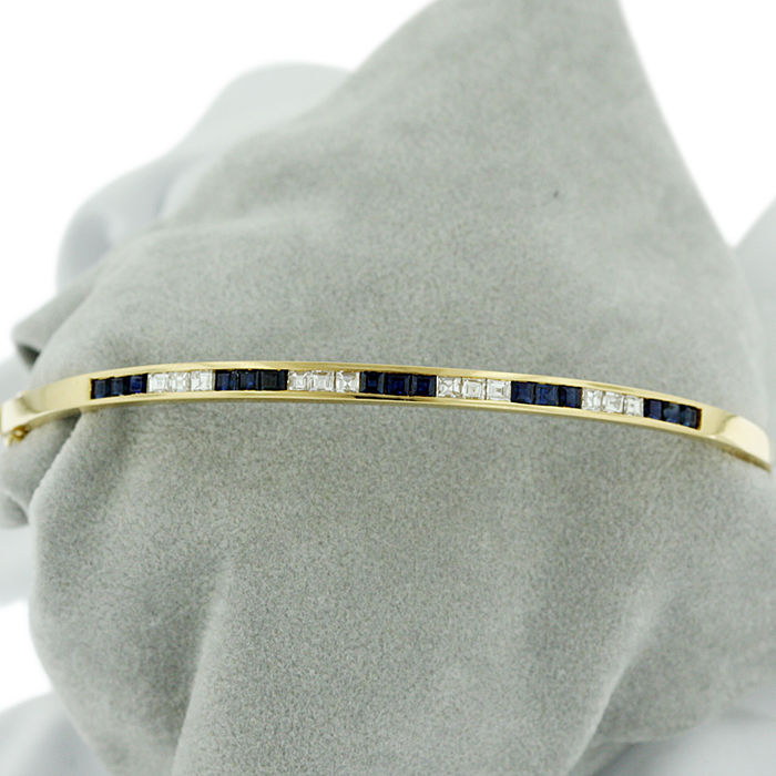 18kt yellow gold Diamond (0.60ct) and Sapphire Bangle in Mint Condition. Dimensions: 7mm wide
