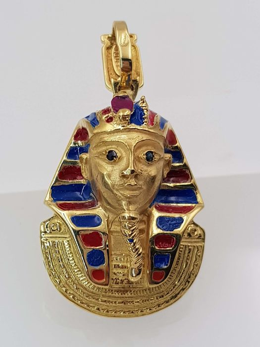 Tutankhamun pendant made of shiny and matte 18 kt yellow gold with blue and red lacquer, 0.10 ct ruby and two sapphires Weight 17.75 g