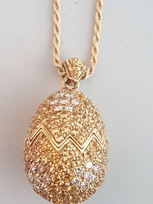 Choker in 18 kt yellow gold with egg shaped pendant that opens in the middle with zigzag edges, and featuring 218 natural yellow sapphires for 5.96 ct and 21 brilliant cut diamonds for 0.50 ct, colour H, clarity VS