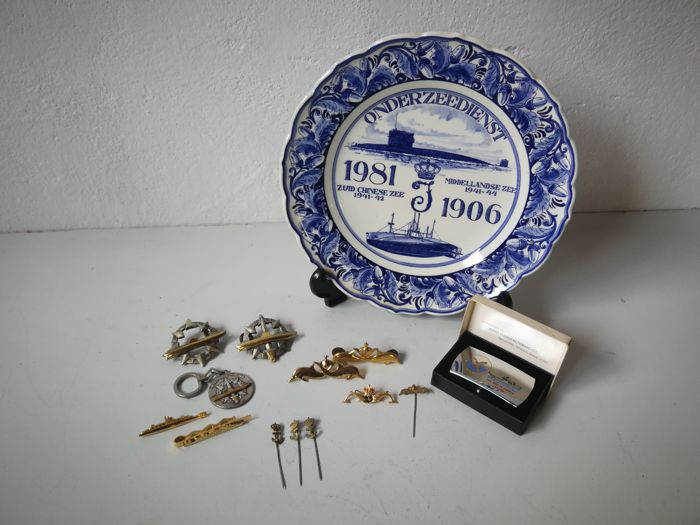 Collection: (Dutch) Royal Navy submarine service; Zippo belt buckle, tie pin, key chain, 4x lapel pin, 2x insignia brooch, 2x lapel pin (brooch), and a wall-plate