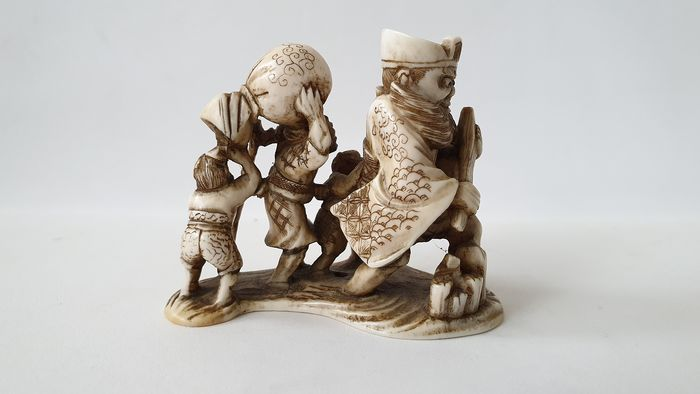 Netsuke - Ivoor - Enma 閻魔 (Sk. Yama), the King of Hell, leading four oni who carry a large bag - Japan - ca. 1880-90s (Meiji-periode)