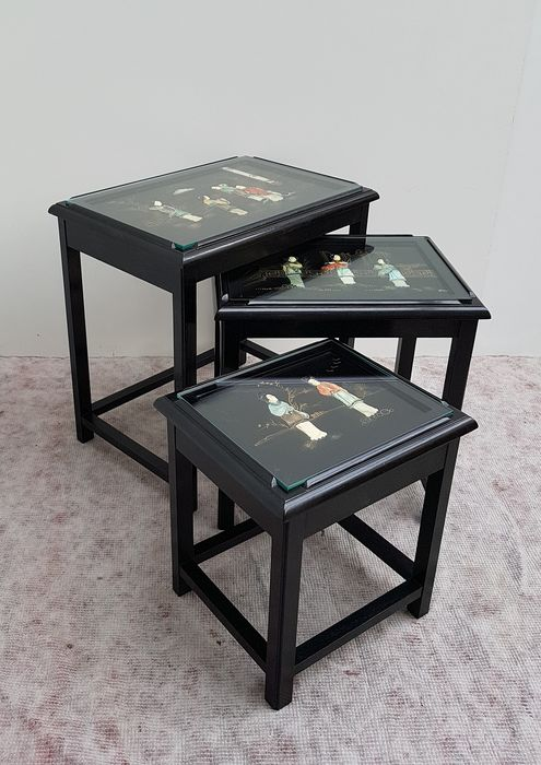 Retractable Chinoiserie tables in three different sizes.