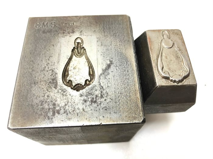 A metal factory ornament pendant stamp - Iron (cast/wrought)