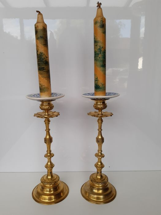 Pair of candlesticks with accompanying waxing candles