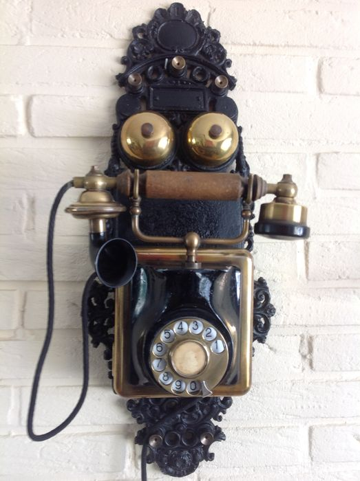 A cast wall phone with copper ornament - Iron (cast/wrought)