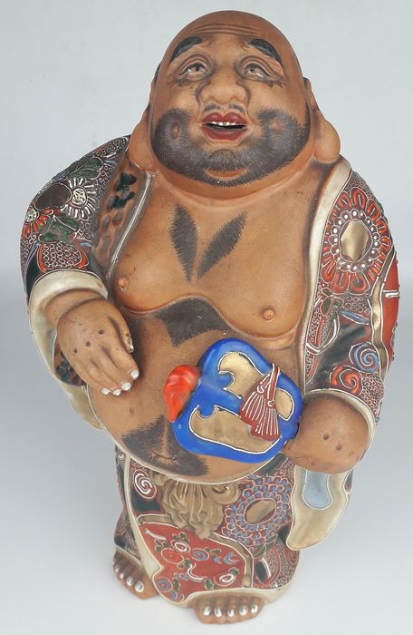 Statue of the God of Good Fortune Hotei carrying his bag of riches and holing a gumbai - Satsuma - Ceramic - Japan - mid 20th century