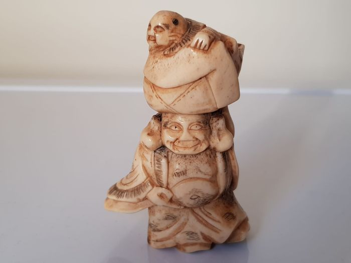 Netsuke - Stag horn  - God of Good Fortune Hotei carrying his bag of riches on his head with a karako on top - Japan - Early 20th century