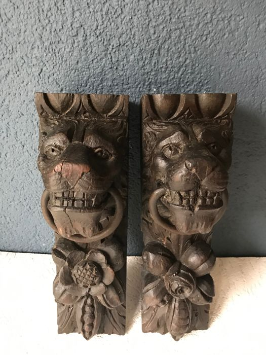 Two carved wood ornaments with a lion s head wood about