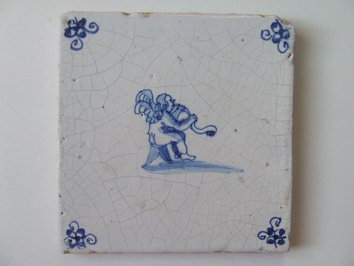 Antique tile with a Music-making Cupid. - Ceramic