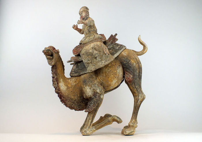 A Masterpiece, Mingqi - Terracotta - Extremely Rare Large Pottery Crouching Bactrian Camel and Foreign Rider - H 59 cm., L 46 cm. TL test - China - Tang Dynasty (618-907)