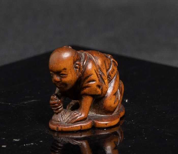Netsuke (1) - Madera - Kneeling man brushing the ground  - Japón - Periodo Edo (1600-1868)