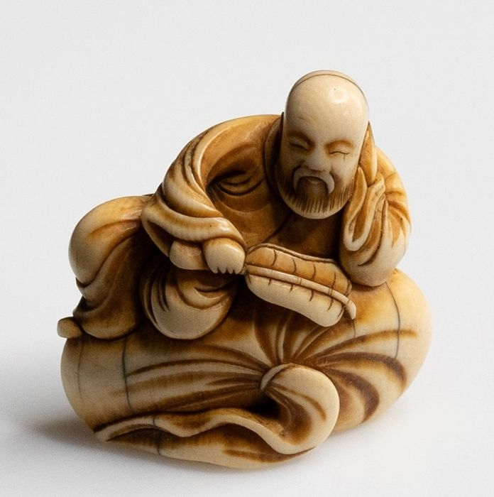 Netsuke (1) - Ivory - AN EARLY NETSUKE OF A CHINESE SAGE ON A LARGE BAG  - Japan - Edo Period (1600-1868)