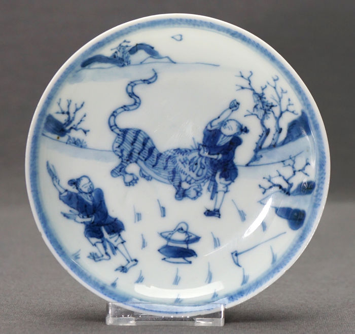 Piattino - Porcellana - two persons fighting a tiger in mountainous landscape - Cina - Kangxi (1662-1722)