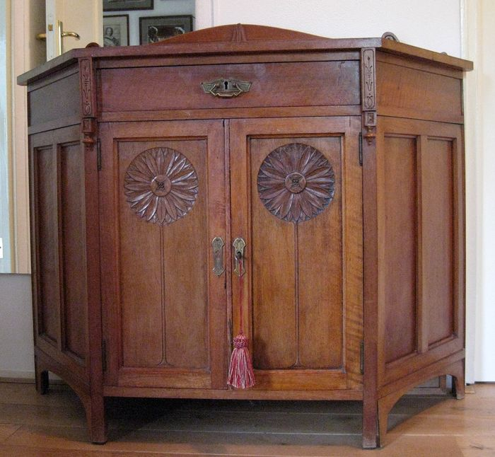 Art Nouveau wall cupboard with stylized carving of sunflowers