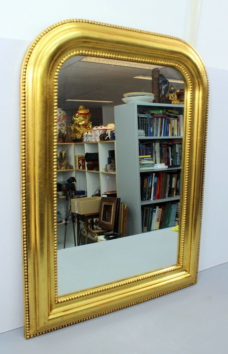 A gold-plated hall mirror with a pearl rim