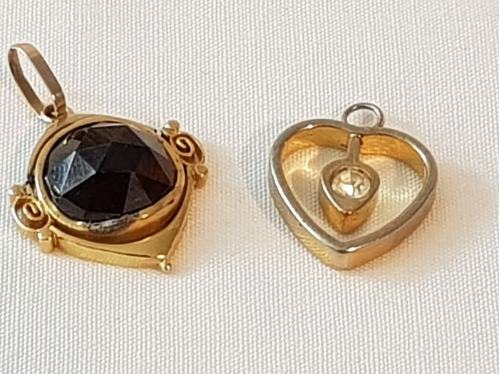 14 karat gold - Two gold pendants, 14 karat, namely one with a facet cut garnet and one heart-shaped pendant with a sapphire