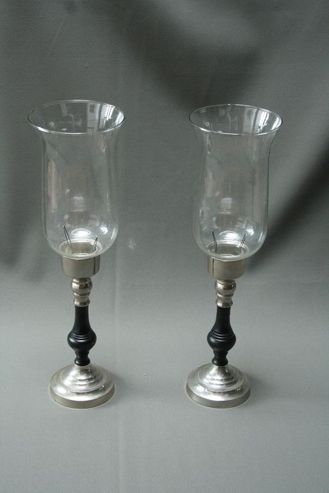 Two Christmas candlesticks with a wooden base and a glass chimney for protection against the wind, made out of wood and metal