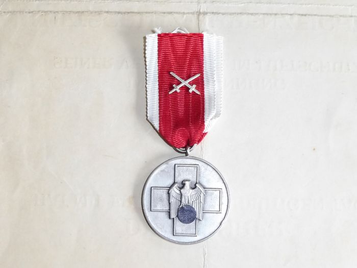 Deutsches Reich - German folk care medal with swords on the ribbon