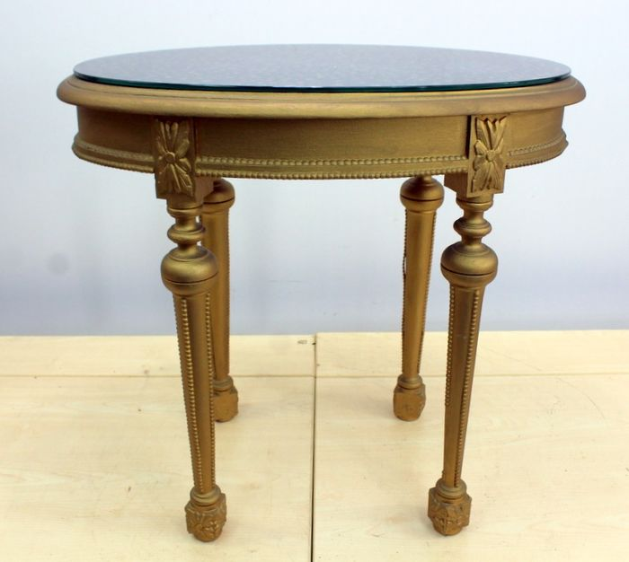 Gold colored side table with metallic glass plate