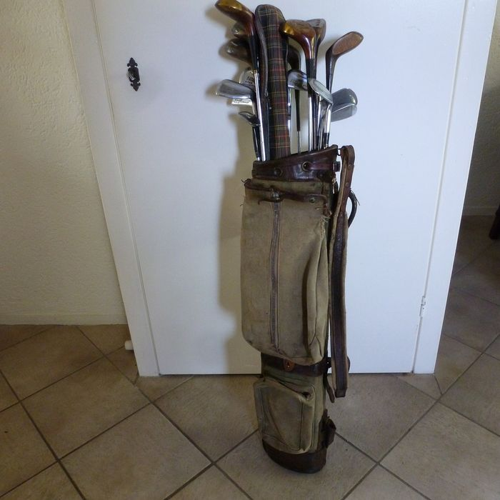 Old golf bag with 17 iron and wooden golf clubs and a golf umbrella - leather and canvas wood and iron