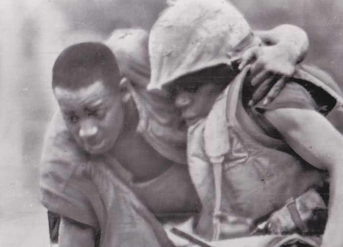 """AP Wirephoto - Marine lifts wounded comrade in """"Leatherneck Square"""" near DMZ, North Vietnam 1967."""