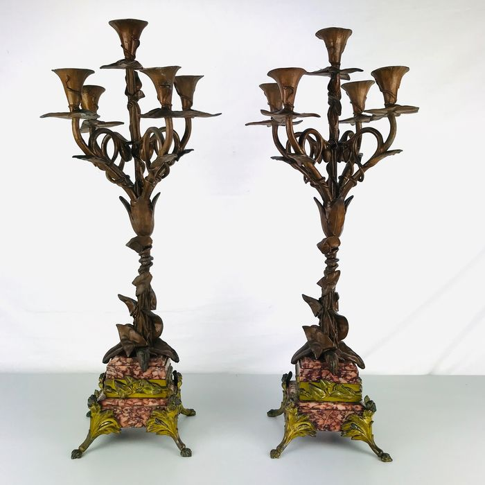 A pair of candlesticks on a red and white veined marble base (63.5 cm) (2)
