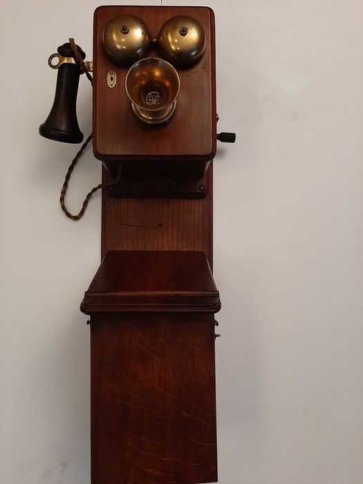 A wooden wall telephone with copper bells and a earpeace - Bakelite, Brass, Copper, Wood- Oak