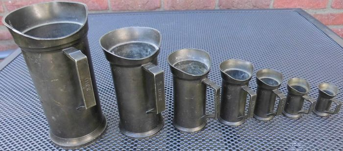 7 pewter measuring cups marked with angel - Pewter