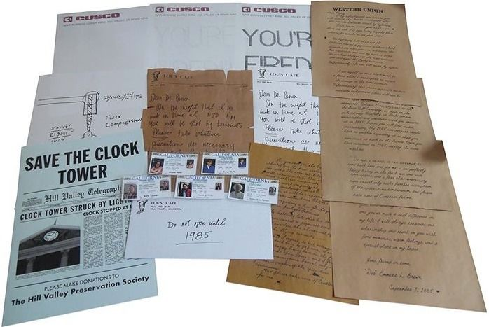 "Back to the Future - Trilogy - Back to the Future - Lot of 12 - Replica Props Letters, Fax, Envelope Lou's Cafe, DeLorean Repair Guide, ""Save the Clock Tower"", IDs and more"