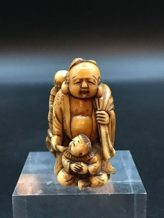 Netsuke, Netsuke Hotei, one of the seven gods of fortune, with his sack accompanied by two children - Ivory - signed : Gyokuun - Japan - Meiji period (1868-1912)