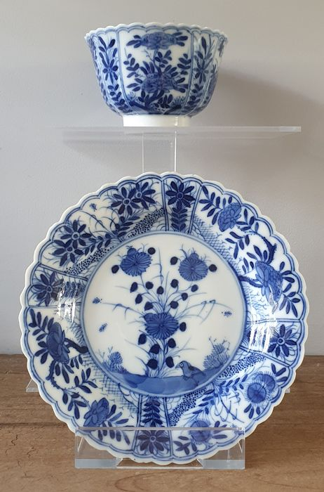Schotel, Theekopje (2) - Blauw en wit - Porselein - Flowers, birds - Scalloped Kangxi cup and saucer, marked with prunusmark. - China - Qing Dynastie (1644-1911)