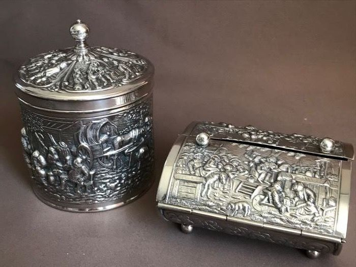 H. Hooijkaas. - Richly decorated tea caddy and box with nostalgic relief. - Silverplate