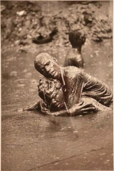 Christina Garcia Rodero (1949) - Two persons in the mud, one holding the other
