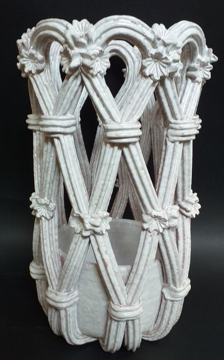 An umbrella stand scrolls with floral weave