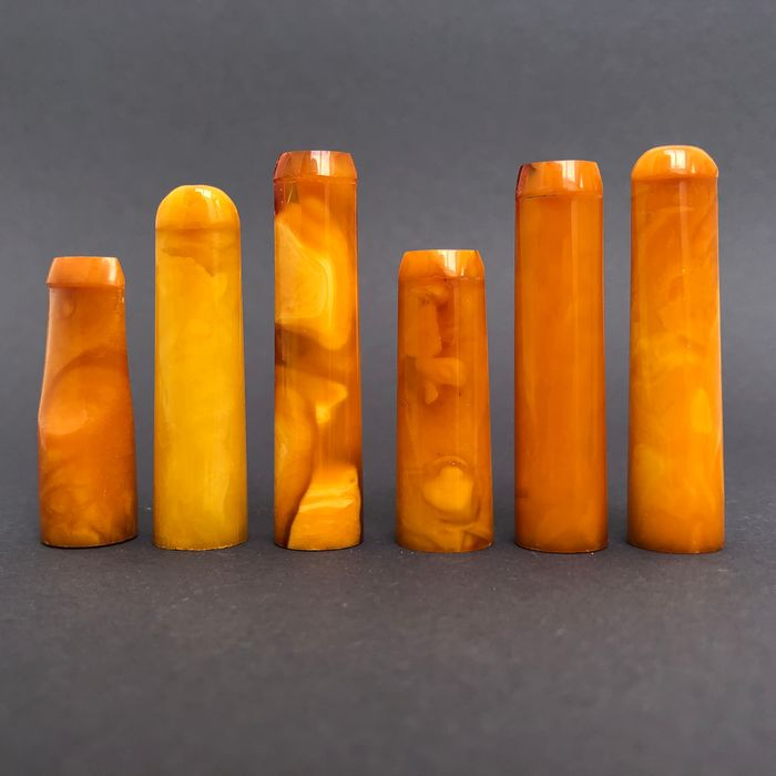 Group of six rock amber pipe stems, old factory stock. Ca. 28 grams.