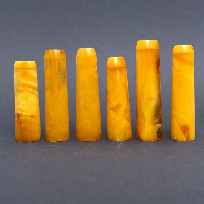 Group of six rock amber pipe stems, old factory stock. Ca. 30 grams.