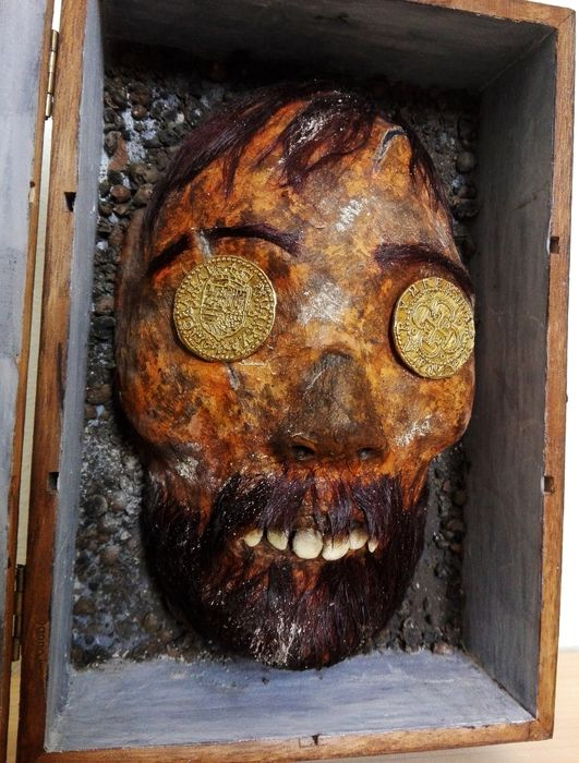 Mummified Head of a Conquistador - with Doublons to close eyes - - In glazed wooden display case - 25×15×10 cm